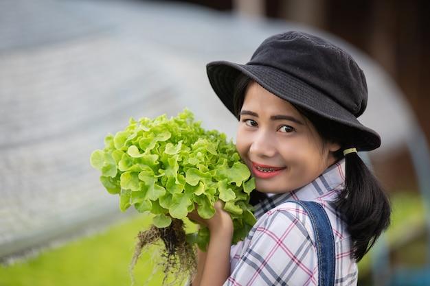 A jovem que está colhendo alface verde no berçário. Foto gratuita