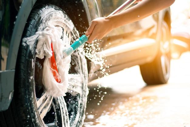 A liga do carro de lavagem do trabalhador do homem roda dentro o cuidado de carro. Foto Premium