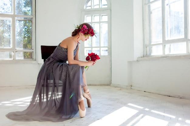 A linda bailarina sentada no vestido longo cinza Foto gratuita
