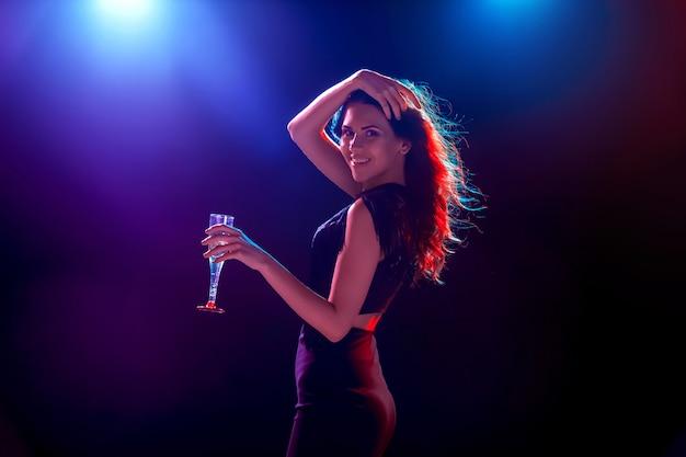 A linda garota dançando na festa e bebendo champanhe Foto gratuita