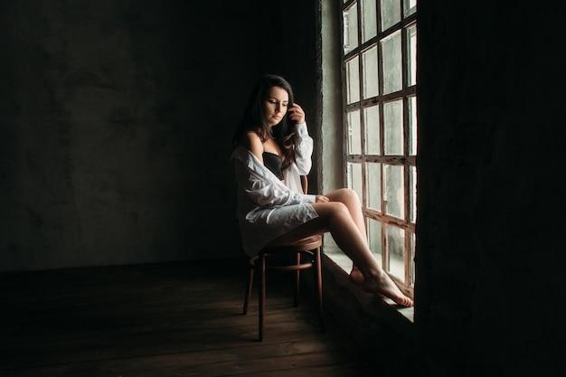 A linda garota se senta na cadeira perto da janela Foto gratuita