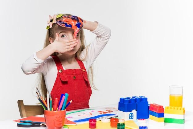 A linda garotinha com as mãos na pintura Foto gratuita