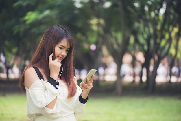 A linda mulher asiática está lendo mensagens de texto agradáveis no telefone celular enquanto está sentado no parque no morno dia de primavera, linda mulher ouvindo música em fones de ouvido e pesquisando informações em celular. Foto gratuita