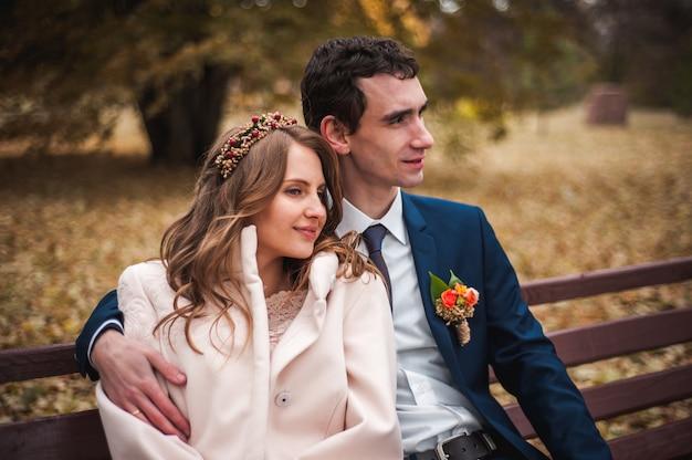 A linda noiva e noivo bonito, sentado num banco Foto Premium