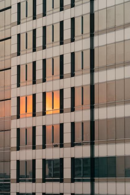 A luz alaranjada do por do sol refletiu na fachada do vidro e do revestimento na noite. Foto Premium