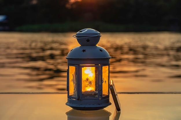 A luz do sol refletindo a água através da lâmpada e telefone celular em cima da mesa. Foto Premium