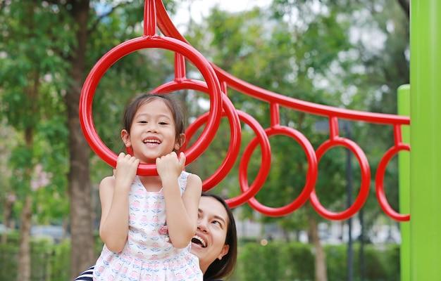 A mãe ajuda sua filha a jogar no anel ginástico no campo de jogos exterior. Foto Premium