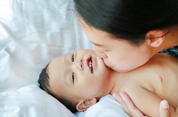 A mãe asiática está jogando e está beijando seu bebê pequeno na cama. Foto Premium
