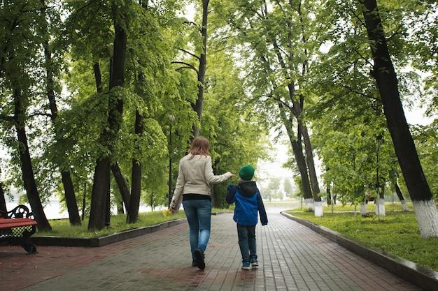 A mãe caminha com o filho no verão, caminha com a família, tradições familiares, amor e compreensão Foto Premium