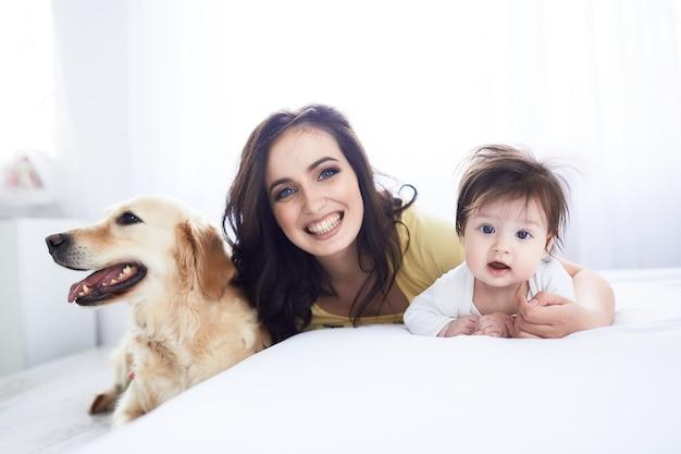 A mãe com a filha deitar na cama e cachorro sentado perto da cama Foto gratuita