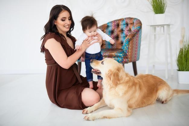 A mãe com a filha sentada no chão e olhando para o cão Foto gratuita