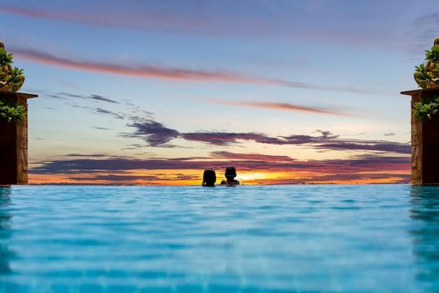 A mãe e o filho novo relaxam no por do sol de observação da piscina sobre o oceano em férias de verão. Foto Premium