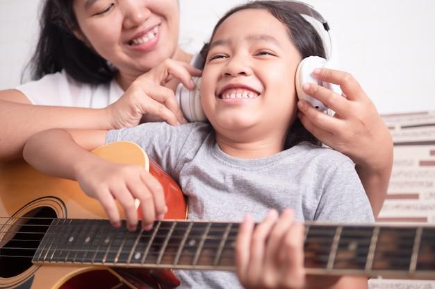 A mãe estava usando fones de ouvido brancos para a menina Foto Premium