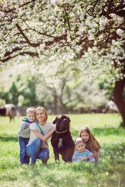 A mãe, filhos e cachorro sentado na grama Foto gratuita
