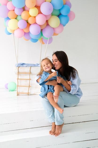 A mãe junto com a filha pequena comemora o aniversário. balão de brinquedo grande no fundo. Foto Premium