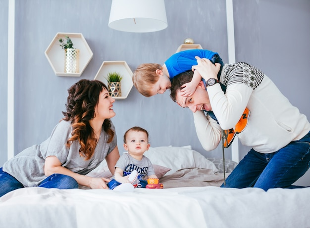 A mãe, pai e filhos sentados na cama Foto gratuita