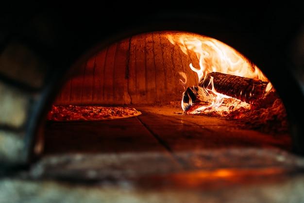A maneira tradicional cozeu a pizza em um forno ateado fogo madeira. Foto Premium