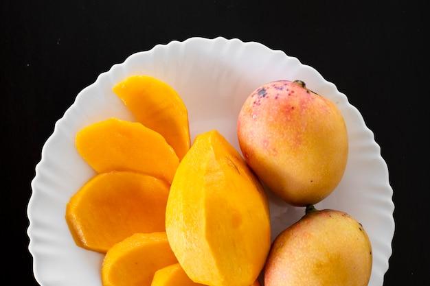 A manga é uma fruta de coloração variada, nativa do sul e sudeste da ásia. foto da manga com um prato branco e um vidro com suco da manga. Foto Premium