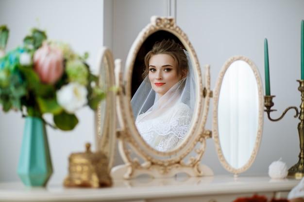 A manhã da noiva. linda garota com um véu branco na cabeça se senta em uma mesa e olha no espelho. Foto Premium