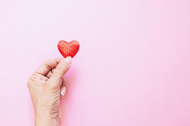 A mão da menina com mini coração vermelho das bolinhas na cor-de-rosa. dia dos namorados. doação de coração. conceito de amor Foto Premium