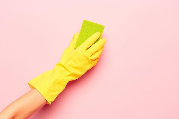A mão da mulher de limpeza em uma parede rosa. conceito de limpeza ou limpeza Foto gratuita