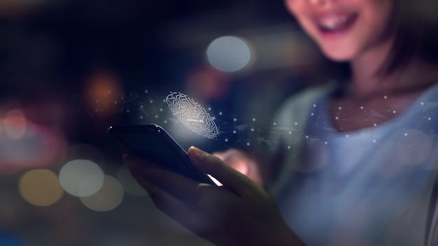 A mão da mulher está digitalizando a impressão digital biométrica para aprovação para acessar o smartphone. Foto Premium