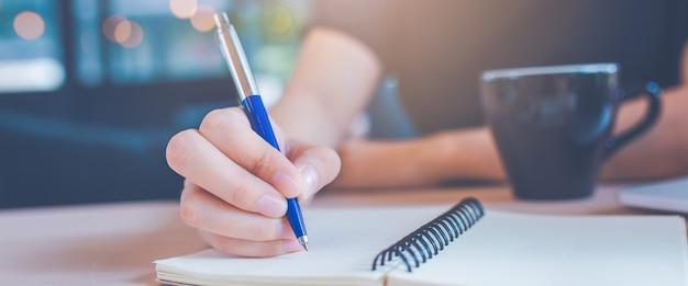 A mão da mulher está escrevendo em um bloco de notas com uma pena no escritório. Foto Premium