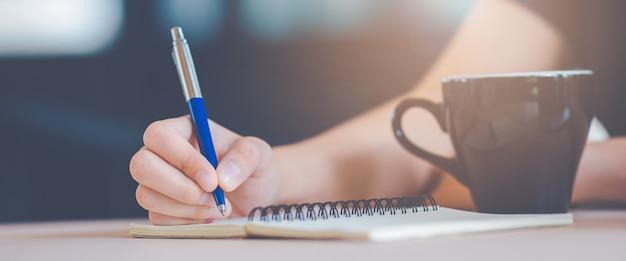 A mão da mulher está escrevendo em um bloco de notas com uma pena. Foto Premium