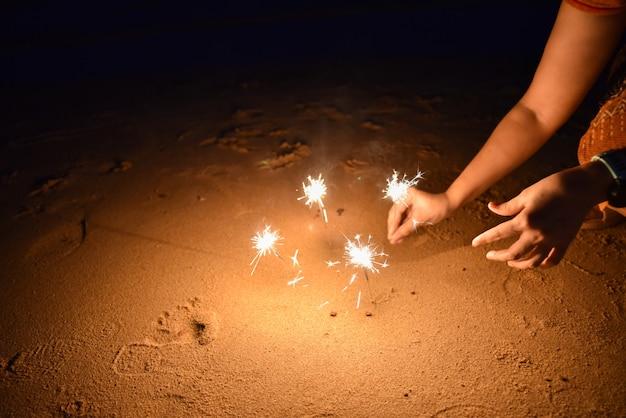 A mão da mulher que guarda chuveirinhos na praia para comemora. Foto Premium