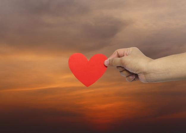 A mão da mulher que guarda um coração vermelho no fundo do por do sol. Foto Premium