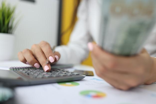 A mão da mulher segura dólares e uma caneta com a outra mão e digita números na calculadora. Foto Premium