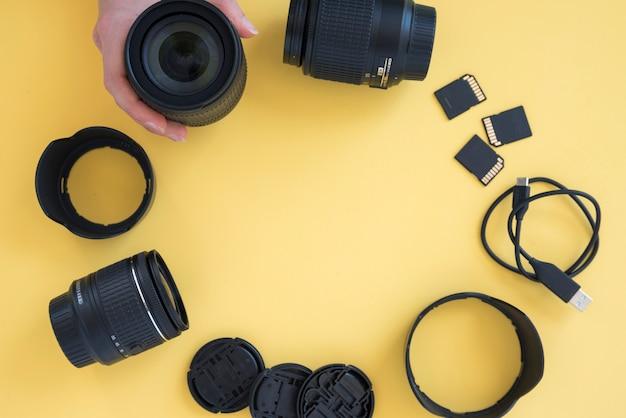 A mão da pessoa que arranja acessórios da câmera na forma circular sobre o fundo amarelo Foto gratuita