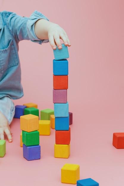 A mão das crianças está construindo uma torre de cubos coloridos de madeira. Foto Premium