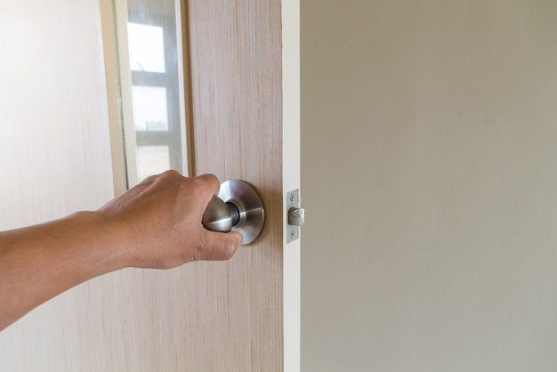 A mão das pessoas abre a porta para dentro, fora da porta aberta colocando na porta da frente Foto Premium