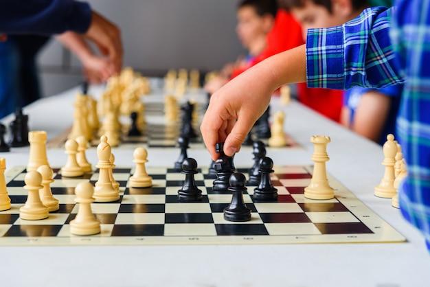 A mão de criança move o cavalo durante um torneio de xadrez com vários tabuleiros de jogo. Foto Premium