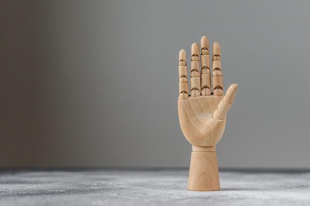 A mão de madeira mostra cinco dedos levantados. o conceito de comunicação Foto Premium