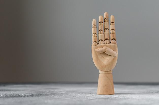 A mão de madeira mostra quatro dedos levantados. o conceito de comunicação. Foto Premium