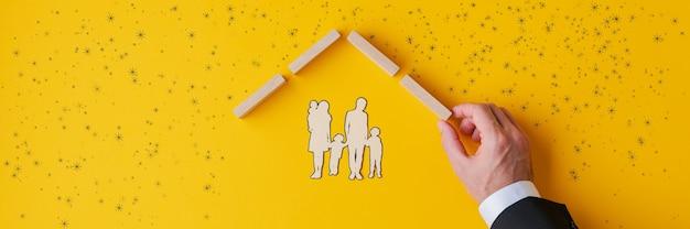 A mão de um agente de seguros abrigando uma silhueta de corte de papel de uma família construindo um telhado de estacas de madeira em uma imagem conceitual de seguros e imóveis. Foto Premium
