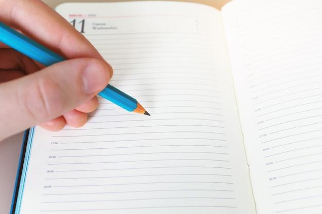 A mão de um homem com um lápis escreve algo em um caderno branco em uma folha em branco. Foto Premium