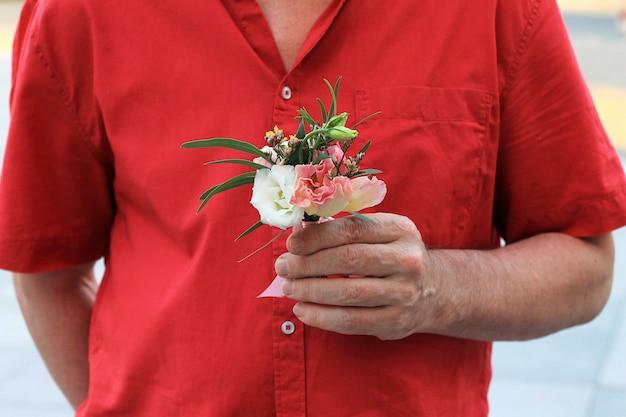 A mão de um homem de camisa vermelha detém um pequeno buquê lindo Foto Premium