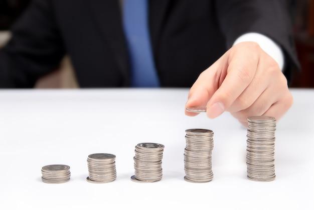 A mão de um homem de negócios acumula moedas. financeiro. Foto Premium