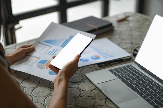 A mão de uma mulher de negócios está usando um telefone celular para encontrar informações. Foto Premium