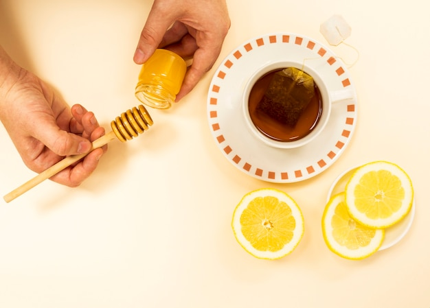 A mão de uma pessoa com um pico de mel de jar para o chá saudável Foto gratuita