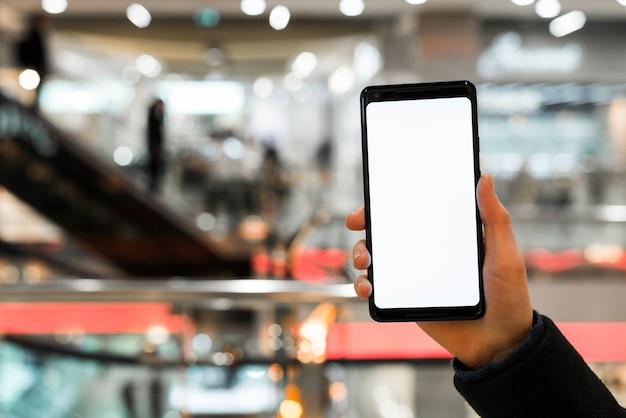 A mão de uma pessoa mostrando a tela do celular no shopping Foto gratuita