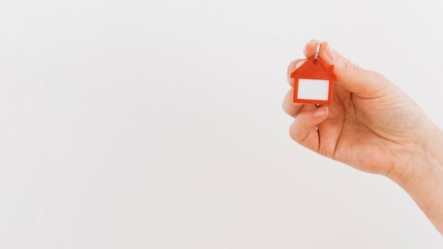 A mão de uma pessoa segurando o chaveiro de casa em pano de fundo branco Foto Premium