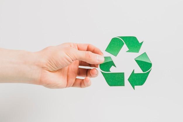 A mão de uma pessoa segurando o ícone verde reciclar isolado no fundo branco Foto gratuita
