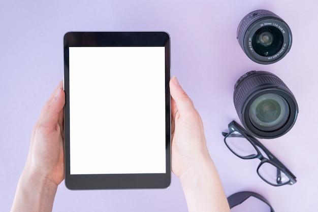 A mão de uma pessoa segurando o tablet digital sobre a lente da câmera e óculos no fundo de lavanda Foto gratuita