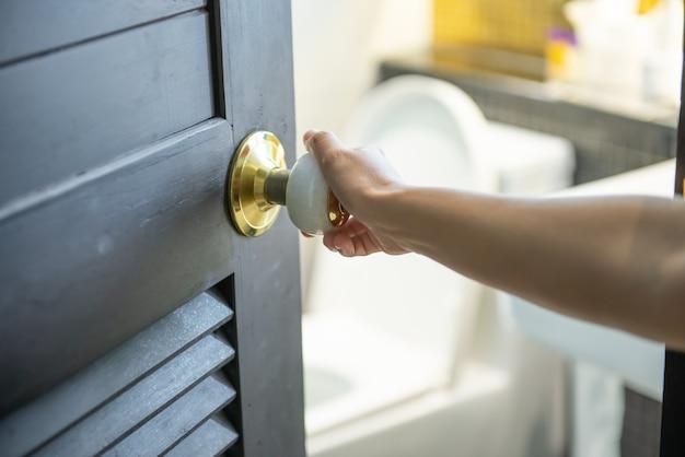 A mão direita da mulher que abriu a porta para o banheiro Foto Premium