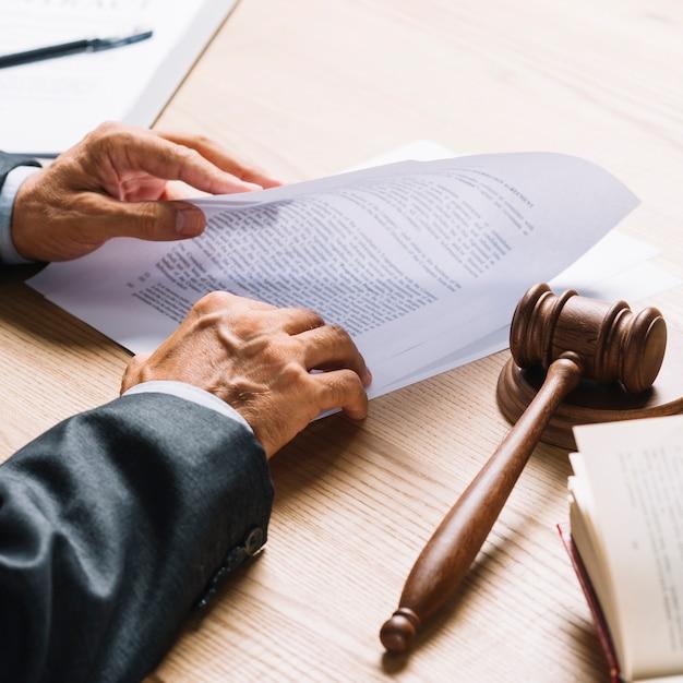 A mão do advogado segurando o documento com martelo e malho na mesa de madeira Foto gratuita