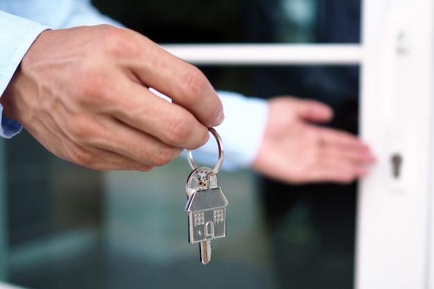 A mão do banqueiro segura a chave da casa. conceito de hipoteca de casa e terra Foto Premium